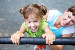 Bild vergrößern: Portrait of a funny little girl hangs by horizontal bar with mother