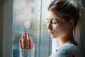 Young girl looking out the window and feeling sad