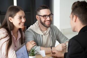 Bild vergrößern: Excited smiling millennial couple discussing mortgage loan investment or real estate purchase with realtor, happy young clients customers being consulted by financial advisor, broker or architect